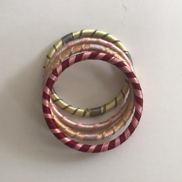 4a0f4c76036da Set of four colorful thread wrapped bangles.